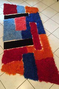 Gefärbte Schaffelle in Patchwork zu einem Teppich in Rautenform verarbeitet