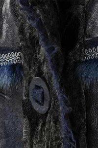 Naturpersianer-Mantel mit blau nappierter Lederseite im Materialmix mit Walkstoff. Detail: Knopf und Borte